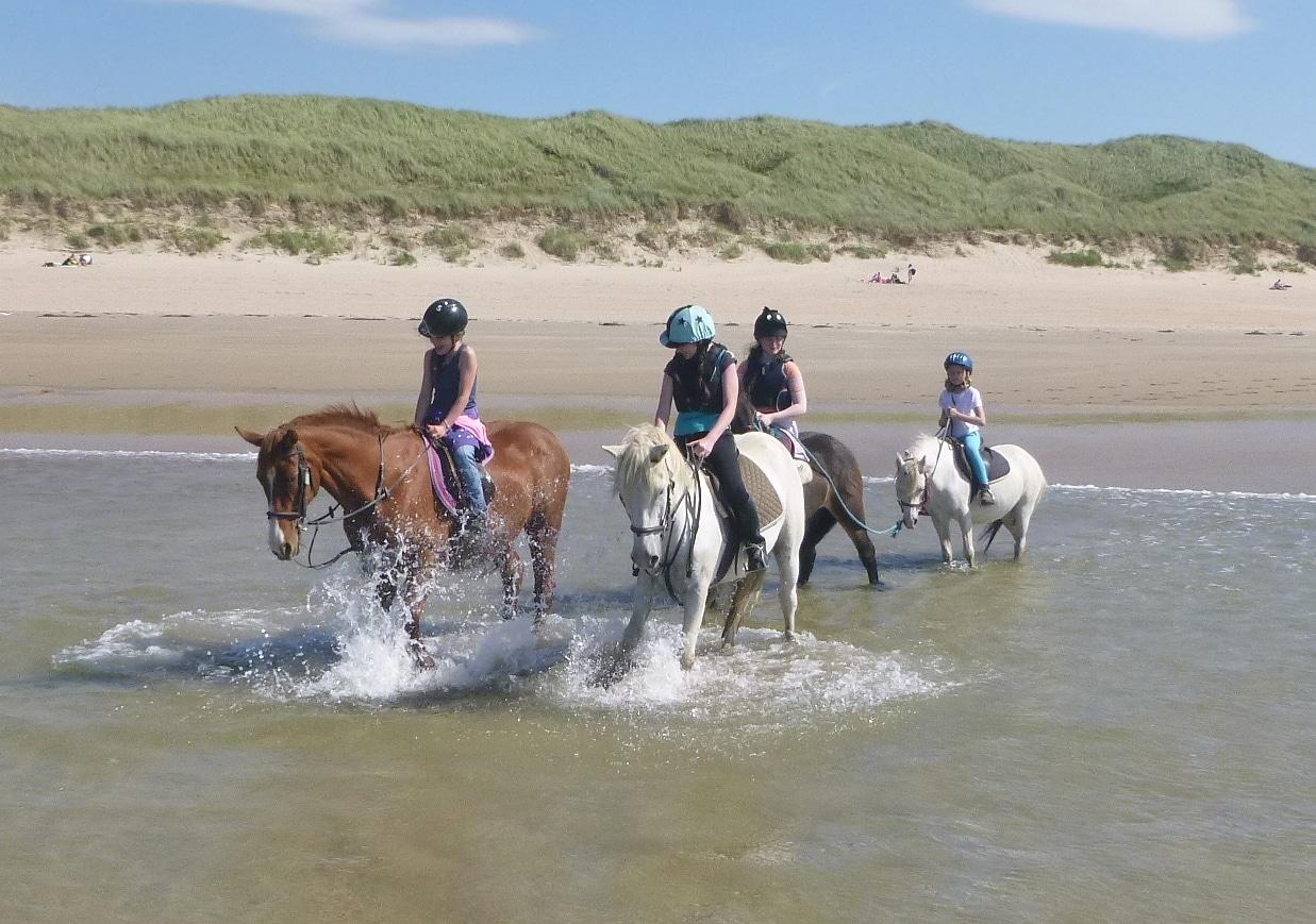 Pony riders splashing in the sea